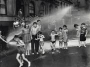 Fotografía en blanco y negro de unos niños refrescándose en la calle