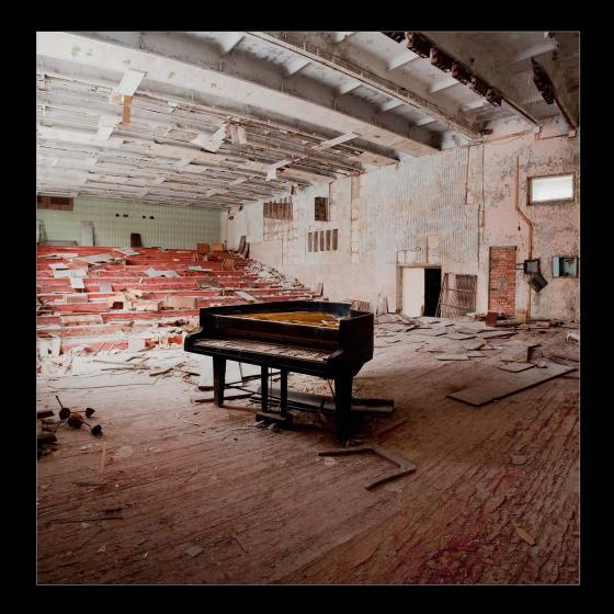 Fotografía de Benítez Barrios en la que se aprecia un auditorio derruido con piano al centro.