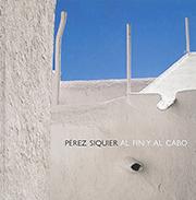 Fotografía en color de una casa mediterránea, de color blanco puro, sobre cielo azul.